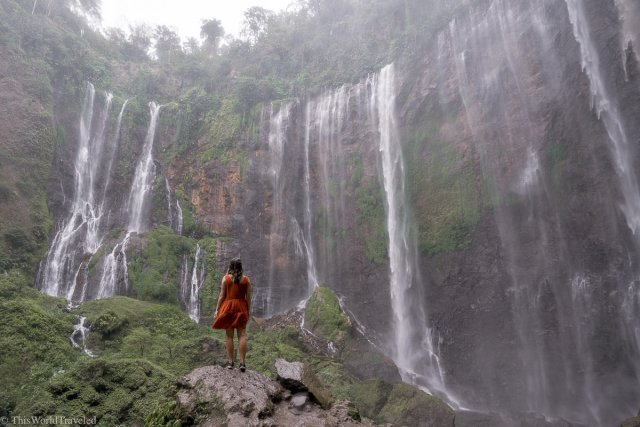 Girl standing in front of Tumpak Sewu Waterfall in East Java, Indonesia