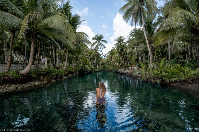 Girl sitting on a rock in the Maasin River watching people swing from the coconut tree on Siargao Island in the Philippines