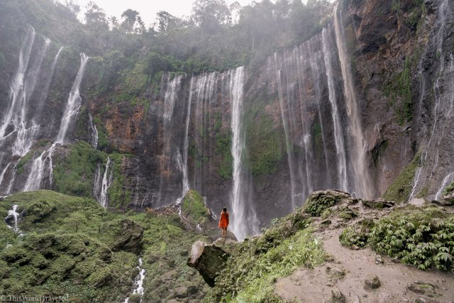 Girl in orange dress standing in front of the powerful waterfall of Tumpak Sewu in East Java, Indonesia