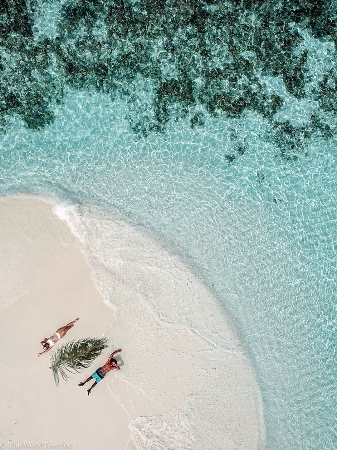 Girl and guy laying on the beach in the Maldives