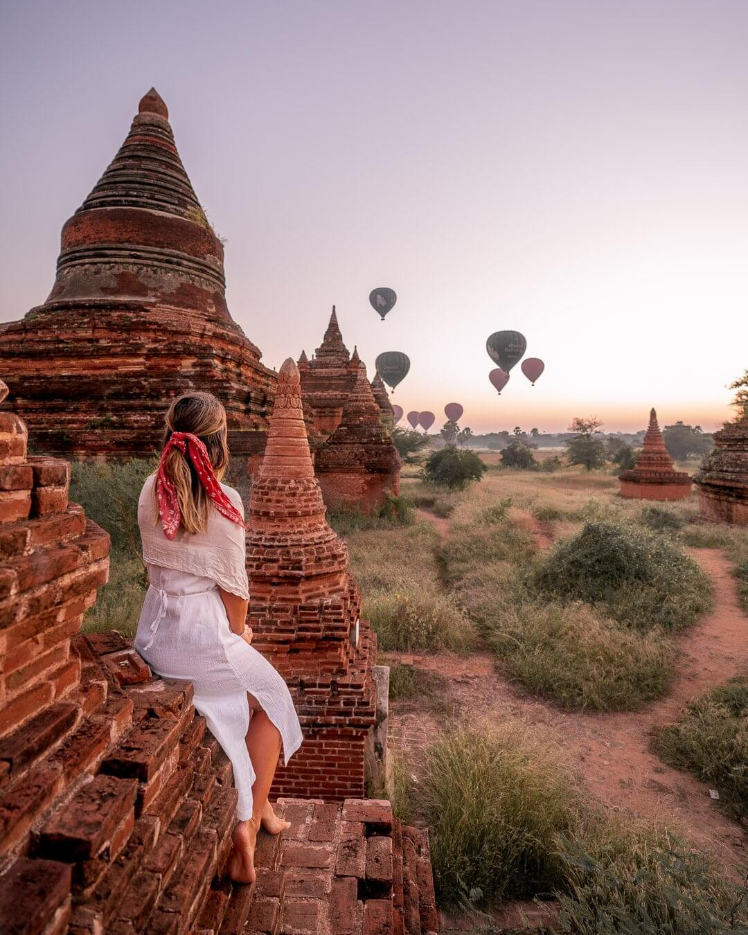 Girl in white dress sitting on a temple in Bagan, Myanmar while the hot air balloons fly overhead at sunrise