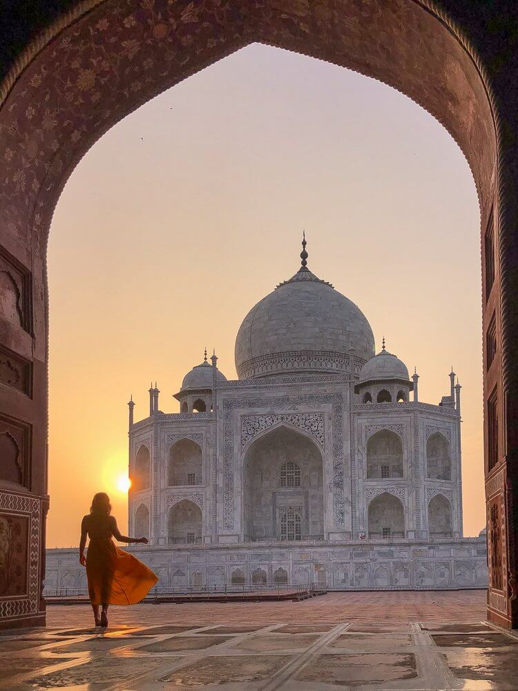 Girl in orange dress standing in from of the arch with a view of the Taj Mahal in Agra, India at sunrise