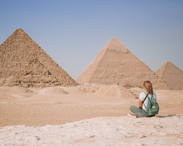 Girl with a green backpack sitting in front of the Great Pyramids of Cairo in Egypt