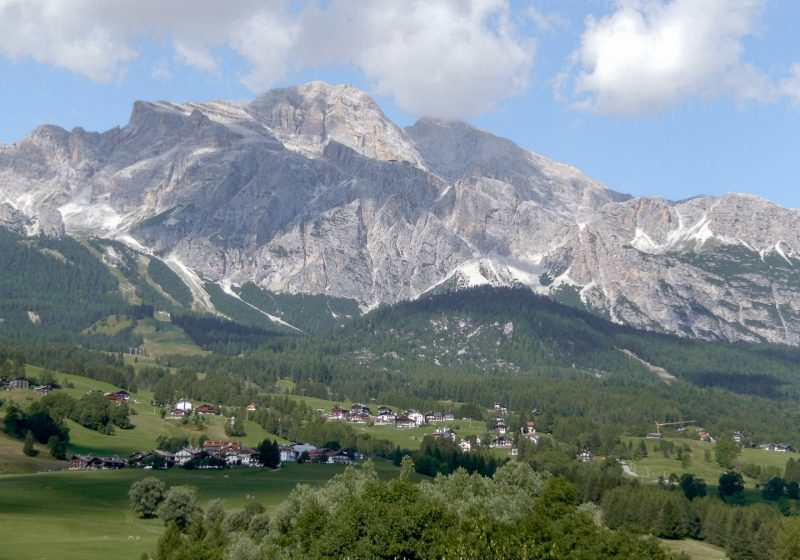 The Dolomites located in northern Italy are a large mountain range surrounded by green vegetation