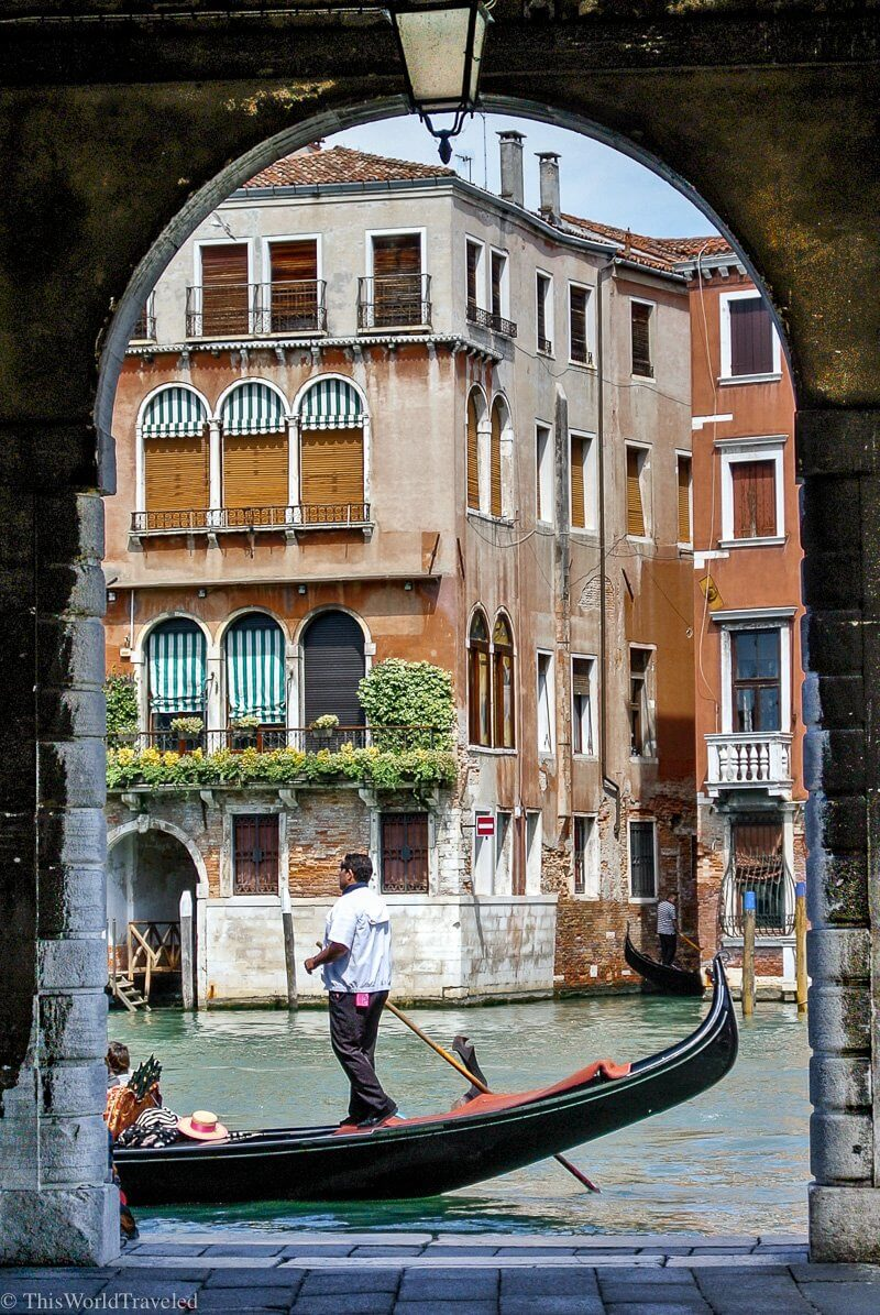 A gondola driving past an archway in Venice, Italy