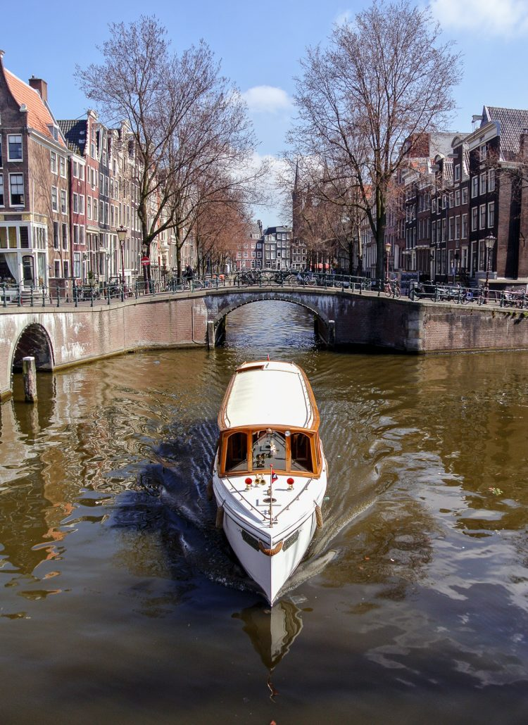 A boat cruising down the canals of Amsterdam in the Netherlands is a fun activity to add when planning a trip to Europe
