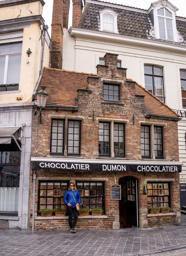A girl in a blue coat standing in front of a chocolate shop in Brugge, Belgium