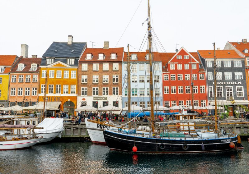 The colorful Nyhavn street in Copenhagen is lines with yellow, red and orange houses.