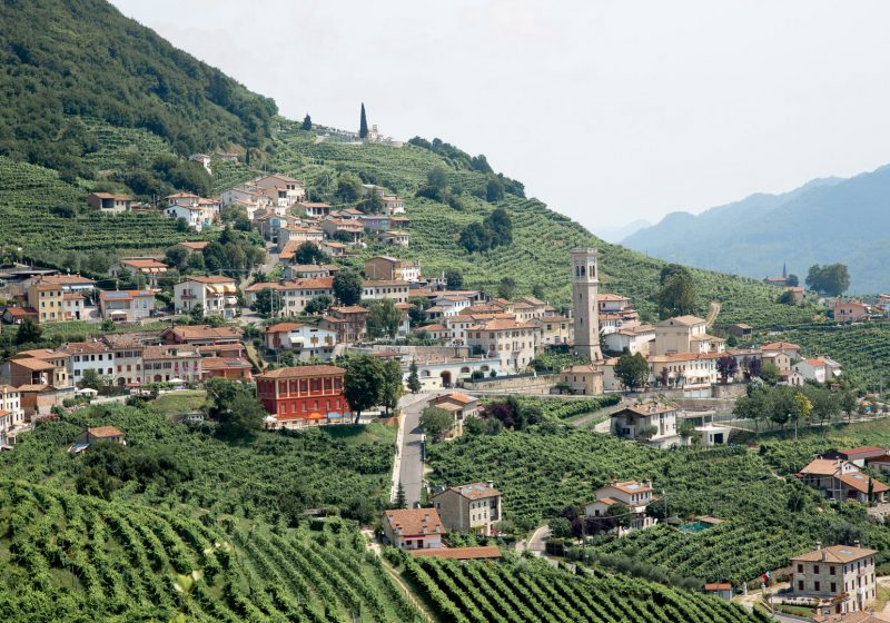 A small village of Italian homes and churches settled amongst rolling hills filled with rows of vineyards in northern Italy's Prosecco Road