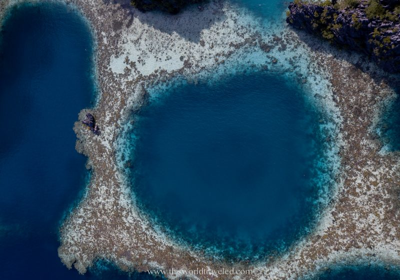 Drone shot of twin lagoon in Coron, Palawan with different shades of blue and a ring-shaped coral reef