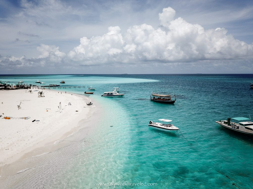 Drone view of a small local island in the Maldives with turquoise water and small wooden boats