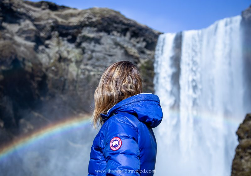 Girl in a blue coat standing in front of the Skogafoss waterfall in south Iceland