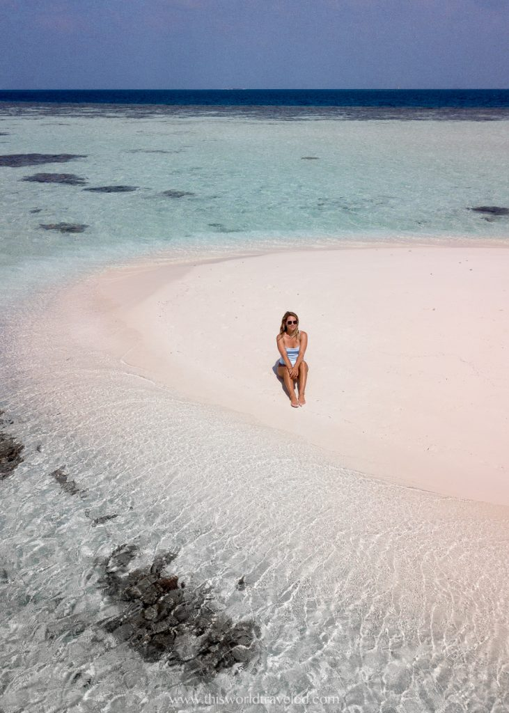A girl sitting in white sand on a private island in the maldives
