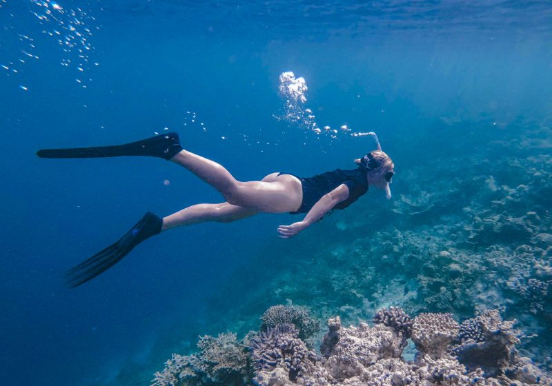 Girl snorkeling in the crystal clear waters of the Maldives