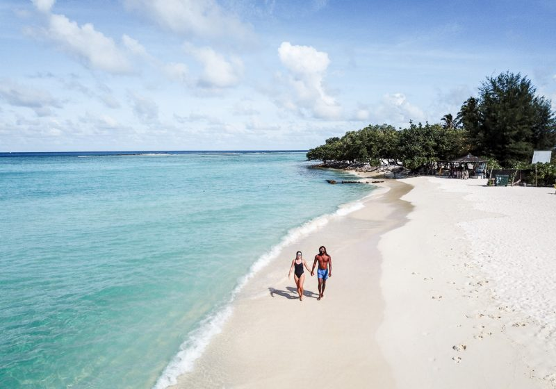 Girl and guy walking along the beach on the island of Gulhi in the Maldives