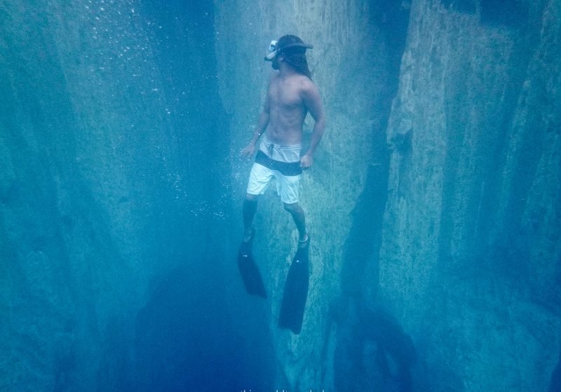 Guy swimming amongst the underwater mountains at Barracuda Lake in Coron
