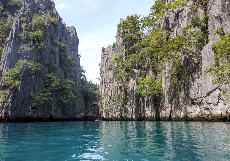 Inside the twin lagoon in Coron, Philippines. The water is blue and is surrounded by limestone cliffs