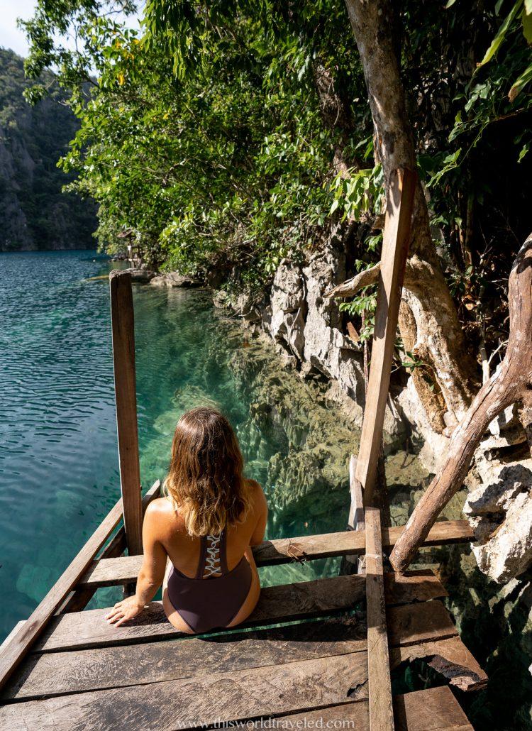 Girl sitting on boardwalk in Kayangan Lake in Coron, Palawan