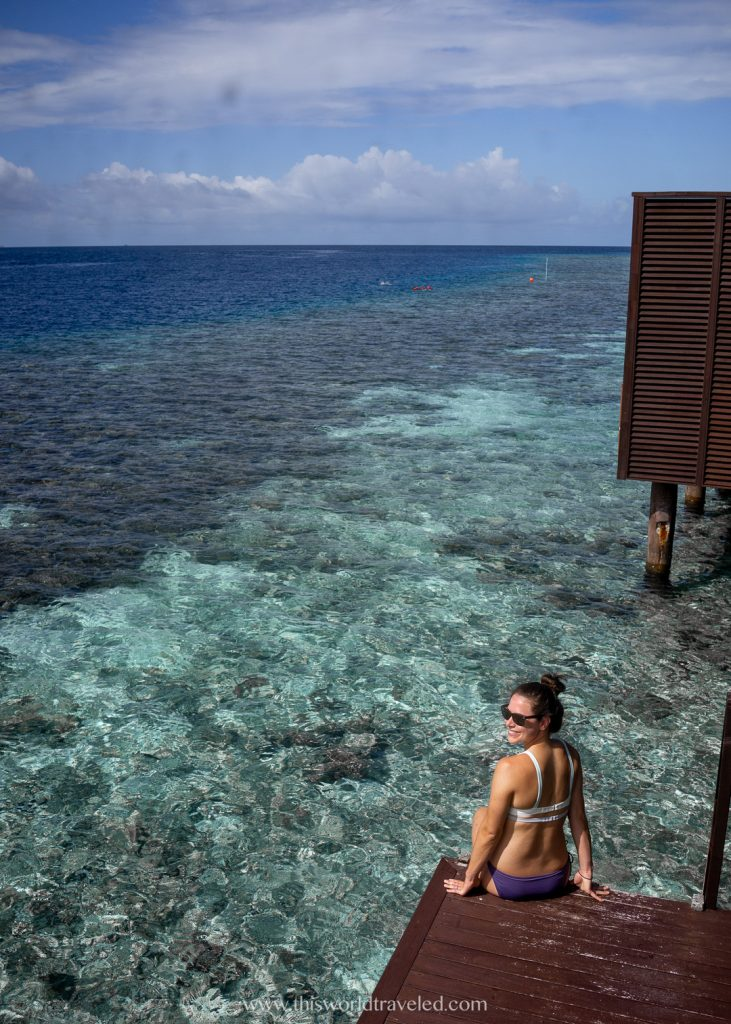 A girl in a swimsuit sitting at the bottom of private steps that lead into the ocean in the Maldives