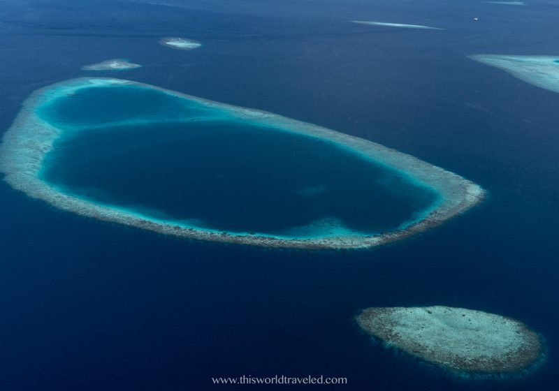 The atolls and coral reefs of the Maldives as seen from a plane in the sky