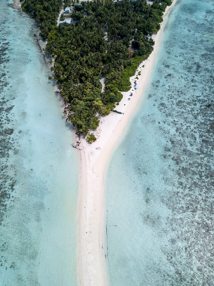 Drone shot of the local island Omadhoo in the Maldives with a long sandbank and lots of palm trees