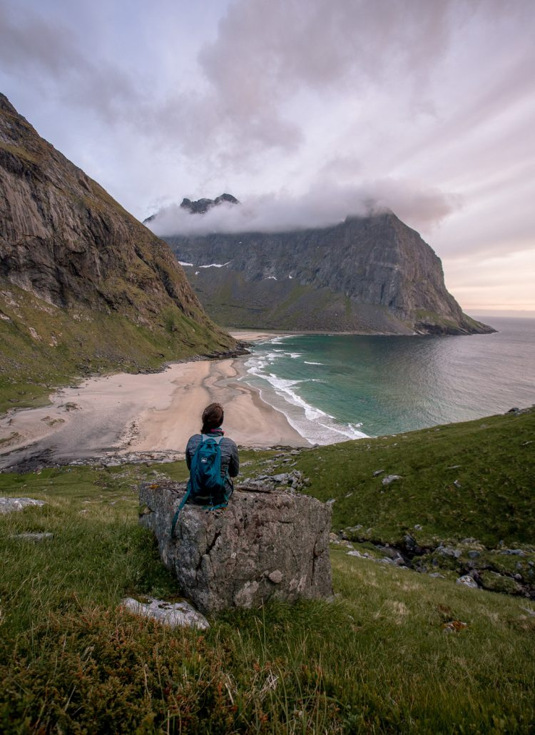 Girl sitting on a rock with the view of Kvalvika beach from the hike up over the hill in the Lofoten Islands