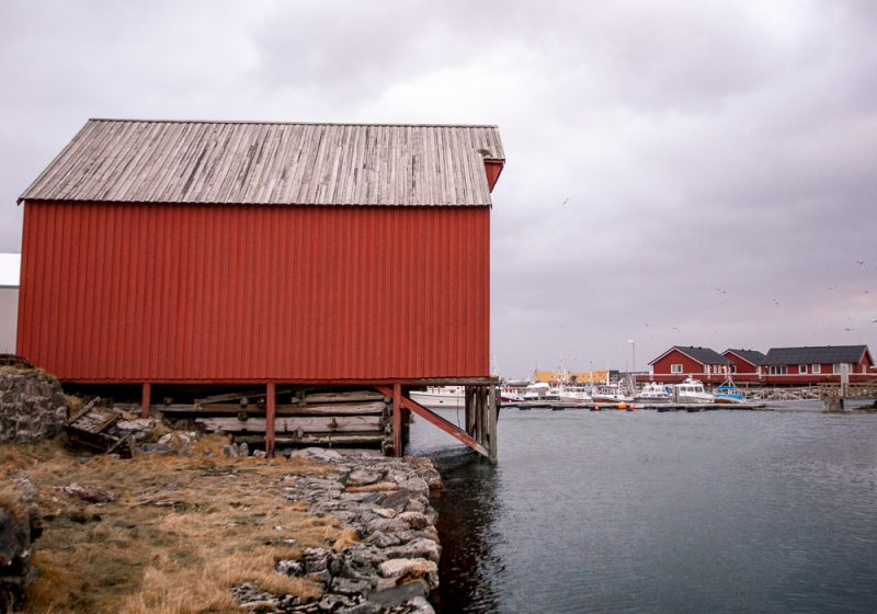 A red fisherman hut on stilts over the water in the small town of Andenes in Norway