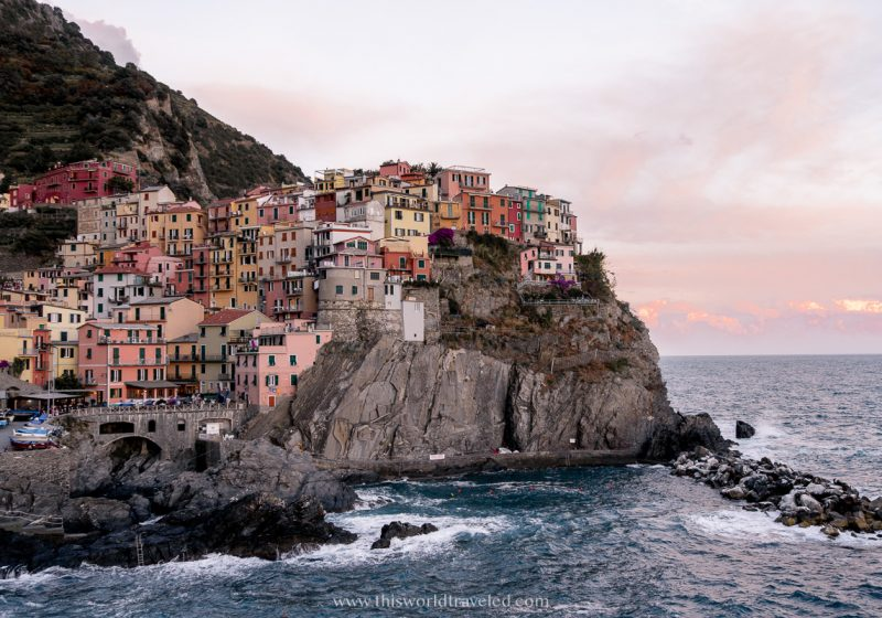 A view of Manarola in Cinque Terre from the Manarola viewpoint in northern Italy's Cinque Terre. The colorful cliffside houses are shades of yellow, orange and pink with a beautiful sunset in the background