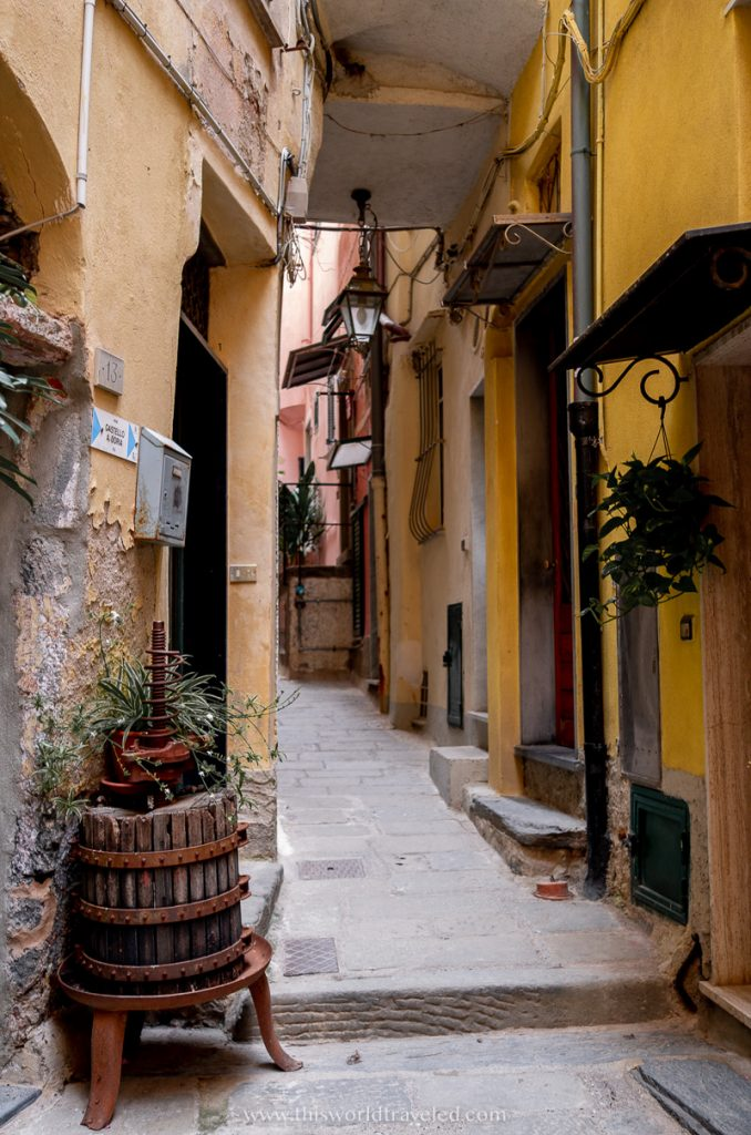 A small alley way in Italy's Cinque Terre village with yellow houses and a narrow street.