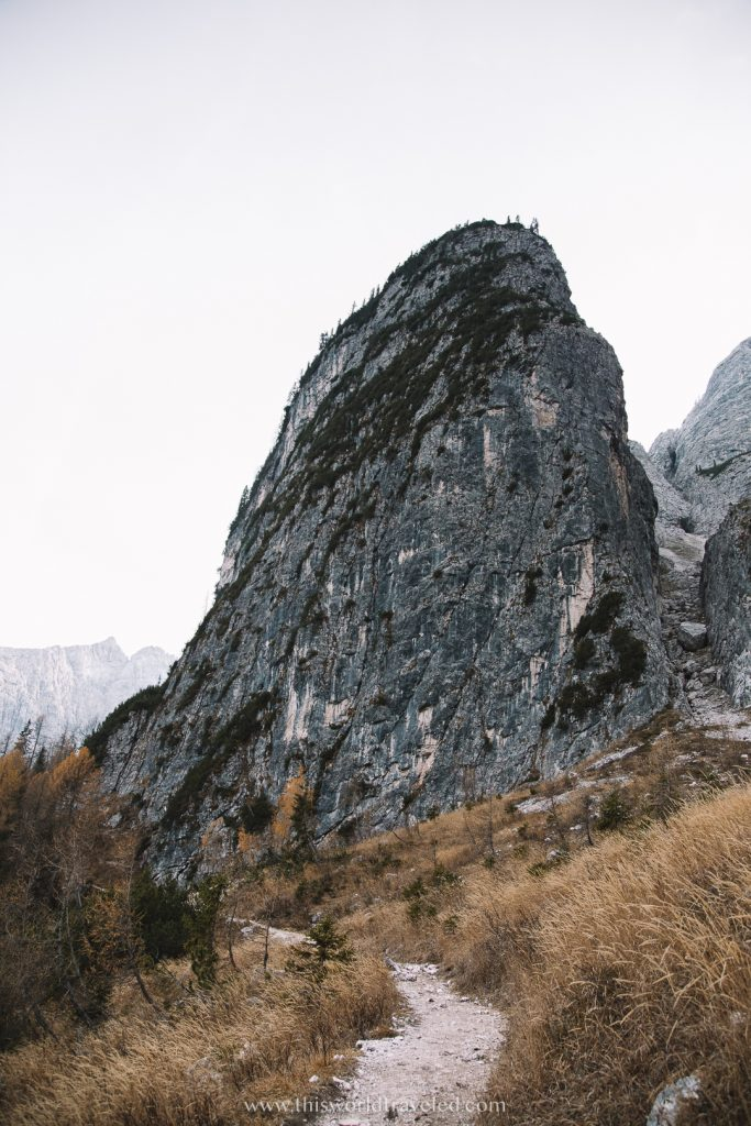 A narrow path leading to a large rock formation along a hiking trail in Italy's Dolomiti mountain range
