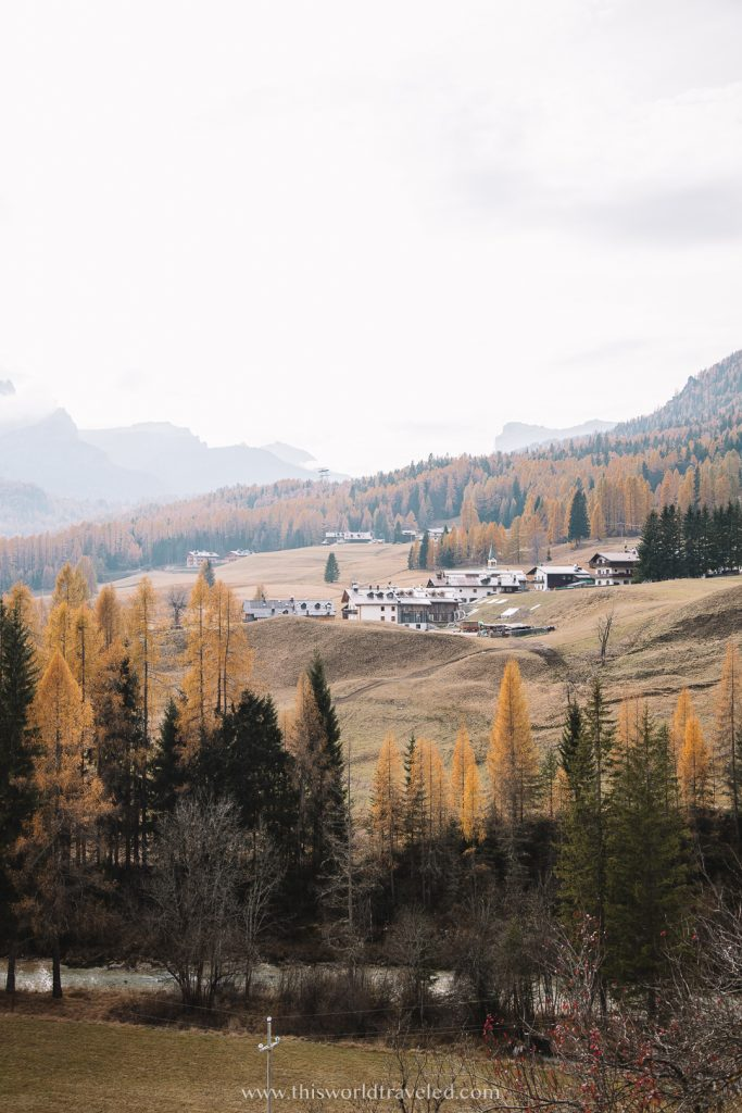 Yellow and green trees with a small town at the foot of the Dolomites in northern Italy