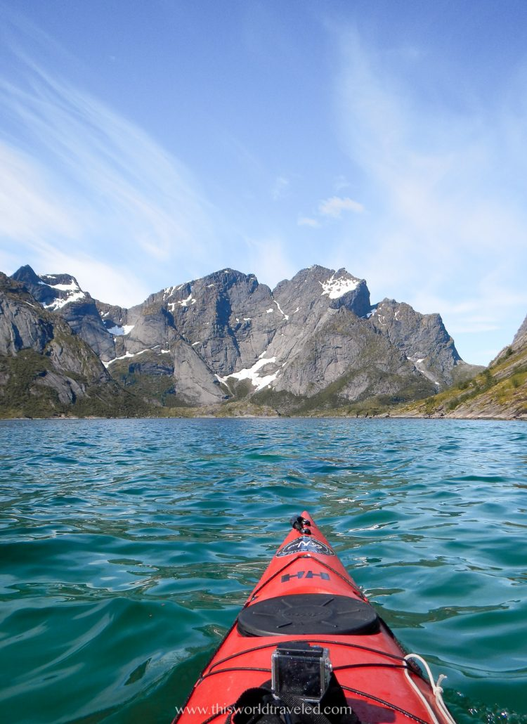 A red kayaking in the Reinefjord in the Lofoten Islands with mountain views