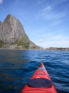 A red kayak in the Reinefjord with a large mountain in the distance