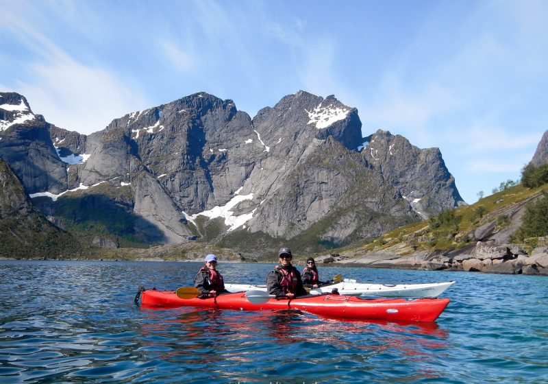 Three girls in kayaks with mountains behind then in the Lofoten Islands in Norway