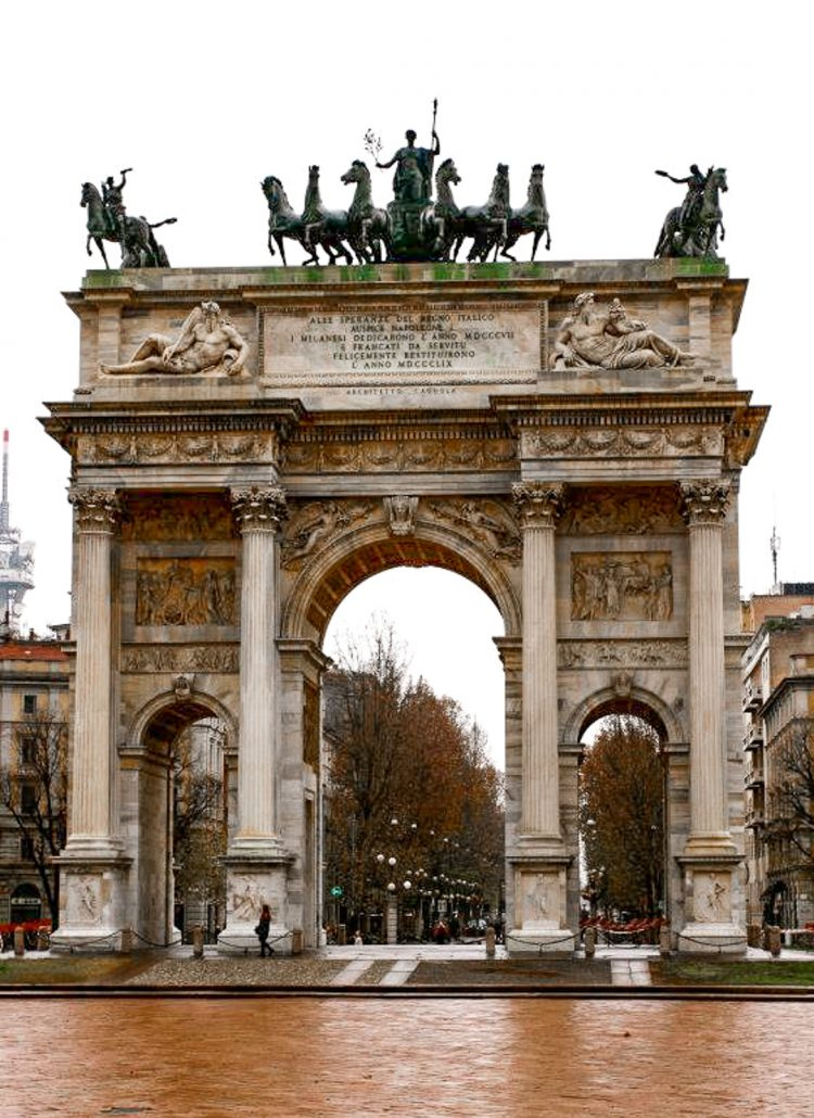 A large archway with statues of horses on the top in Milan, Italy