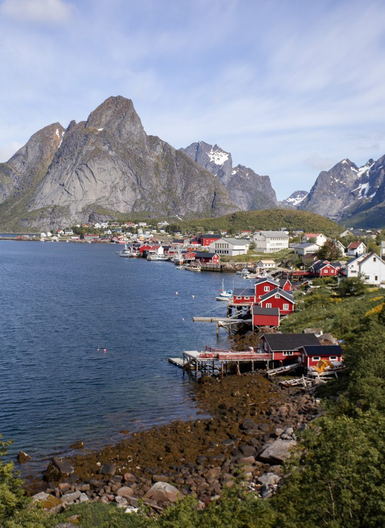 Red fisherman huts along the water with mountains in the back in a town called Reine in Norway