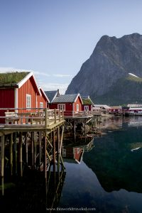 A red Rorbu in Reine that is on stilts over the Reinefjord