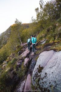 Two girls hiking up a steep and slanted trail in the Lofoten Islands in Norway