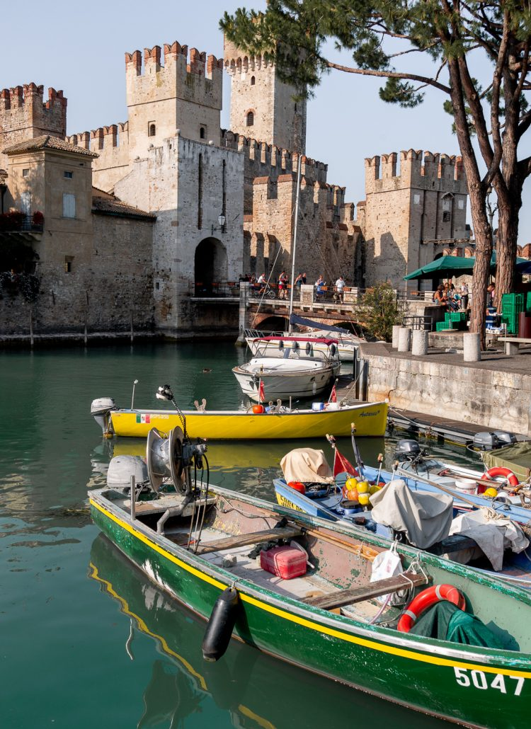 Boats parked in a moat in front of the Sirmione castle in Italy