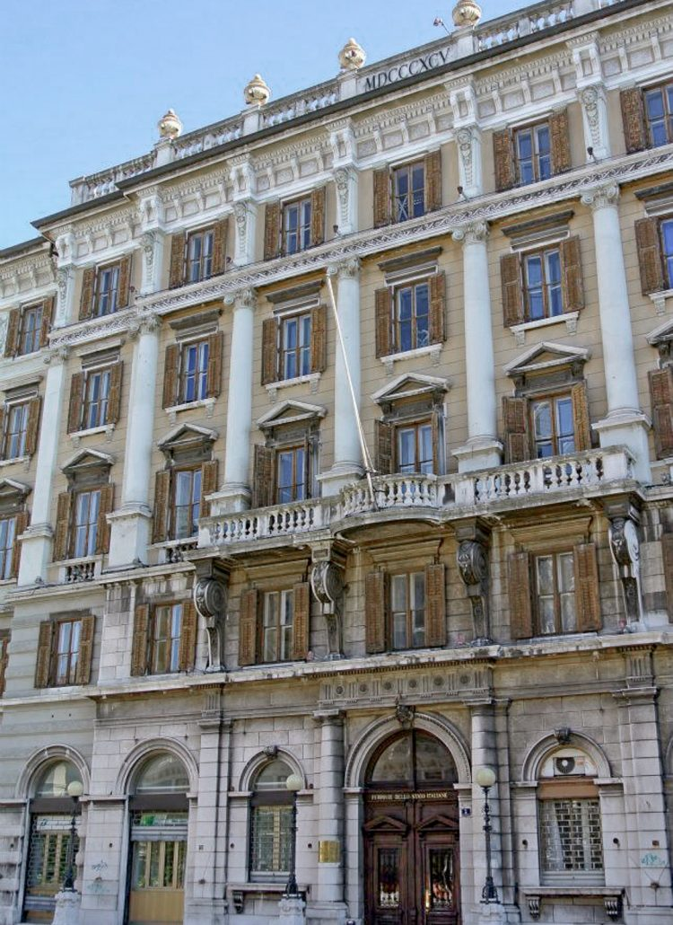A light yellow building in Trieste Italy with ornate details and historic architecture in Trieste, Italy