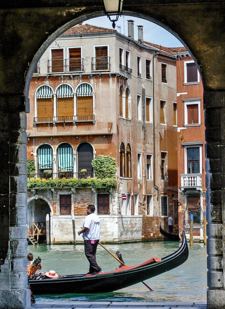 A gondola passing by an archway along the canals in Venice