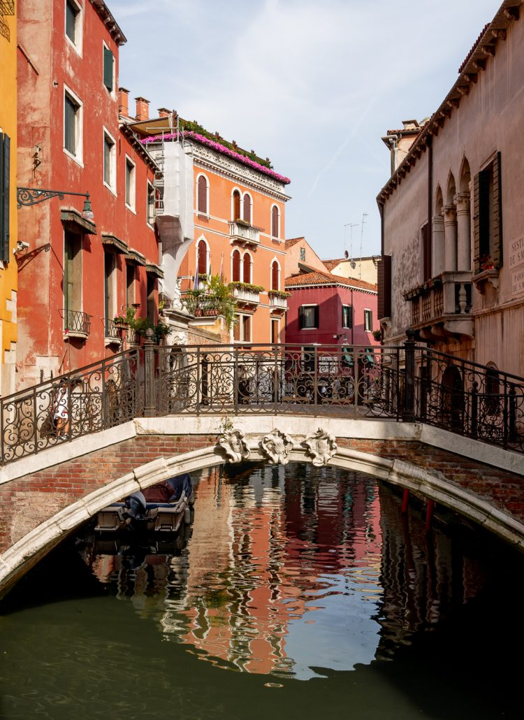 A canal in Venice, Italy with a small pedestrian bridge and orange, yellow and red buildings