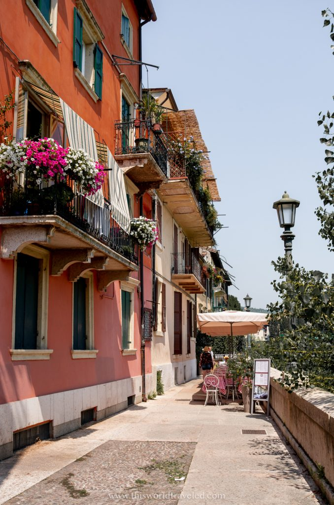 A small street near the river with pink and orange houses in Italy's Verona