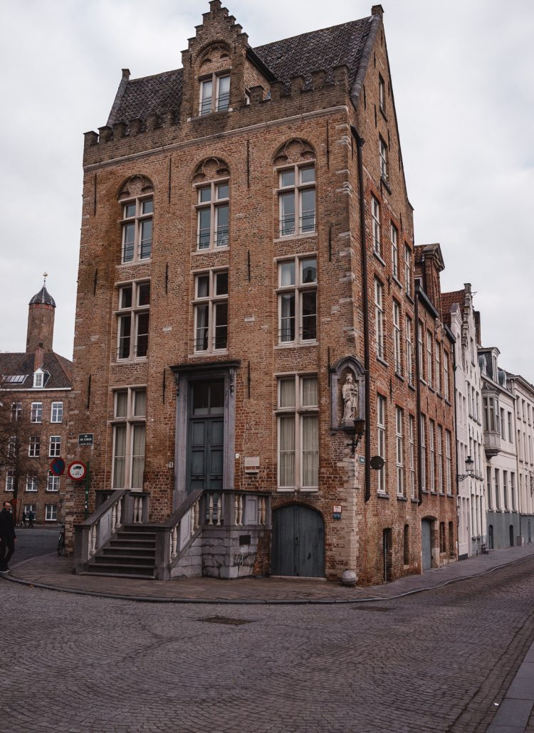 A three story building located along one of Bruges cobblestone streets