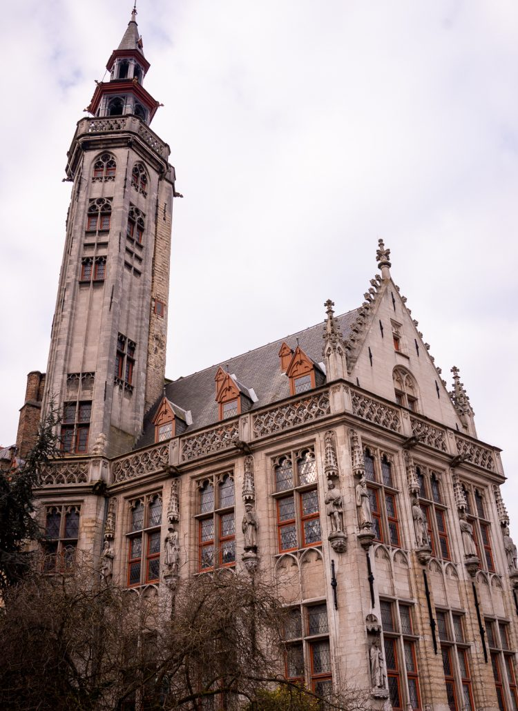 A large church with adornments and a tall bell tower in Bruges, Belgium