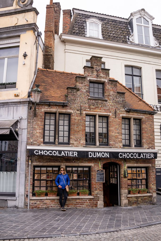 A girl in blue jacket standing outside the Chocolatier Dumon in Bruges, Belgium