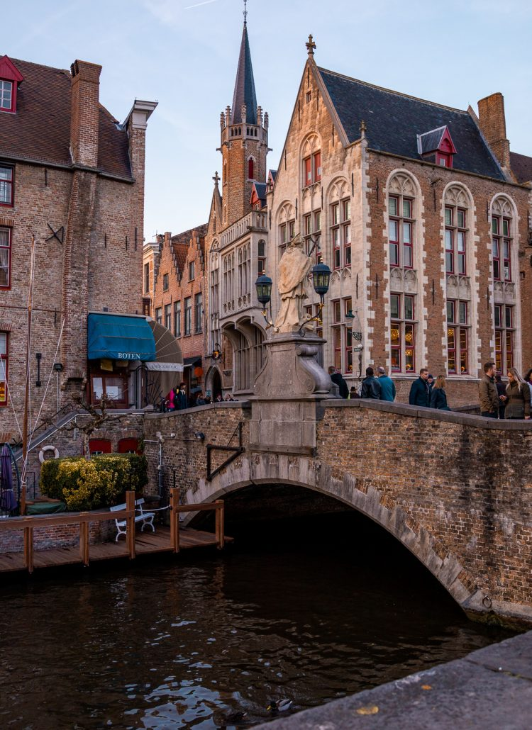 A red-bricked bridge that stretches over a canal in Bruges, Belgium