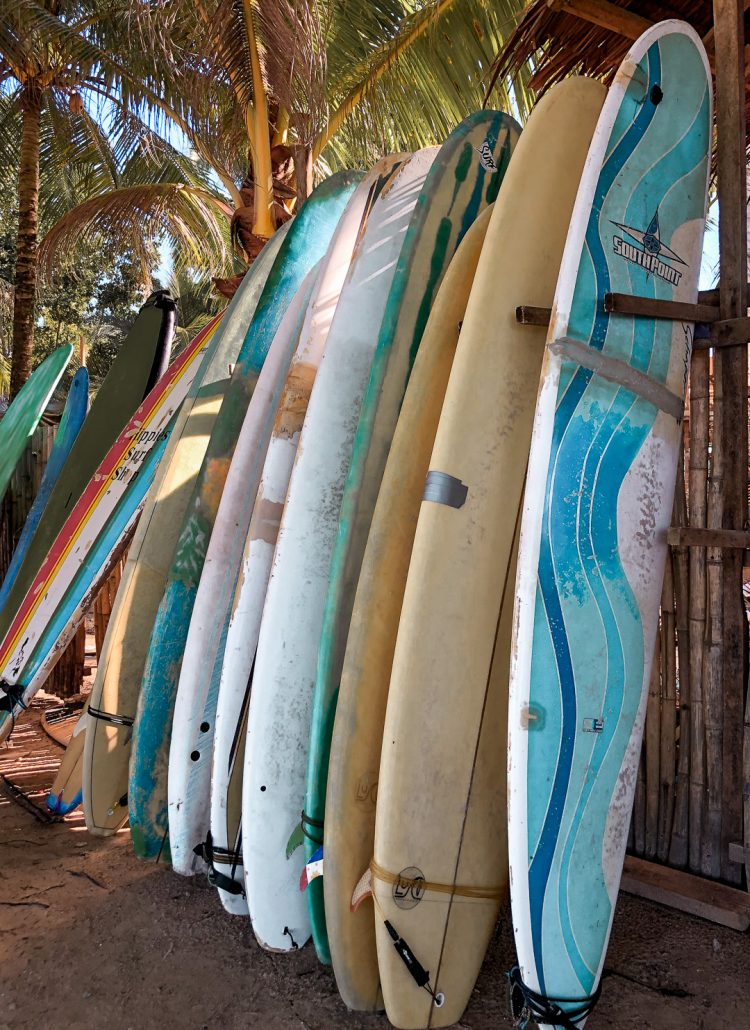 A rack of surfboards in various colors
