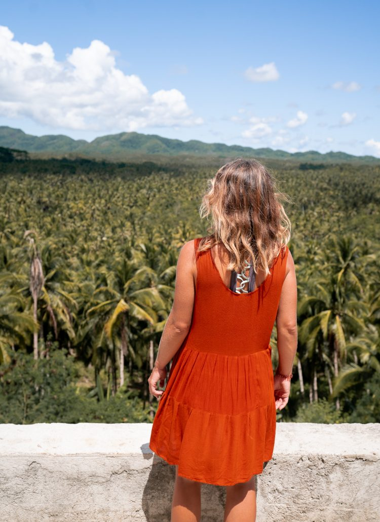 Girl in an orange dress standing on the side of the road overlooking a large forest of coconut palm trees