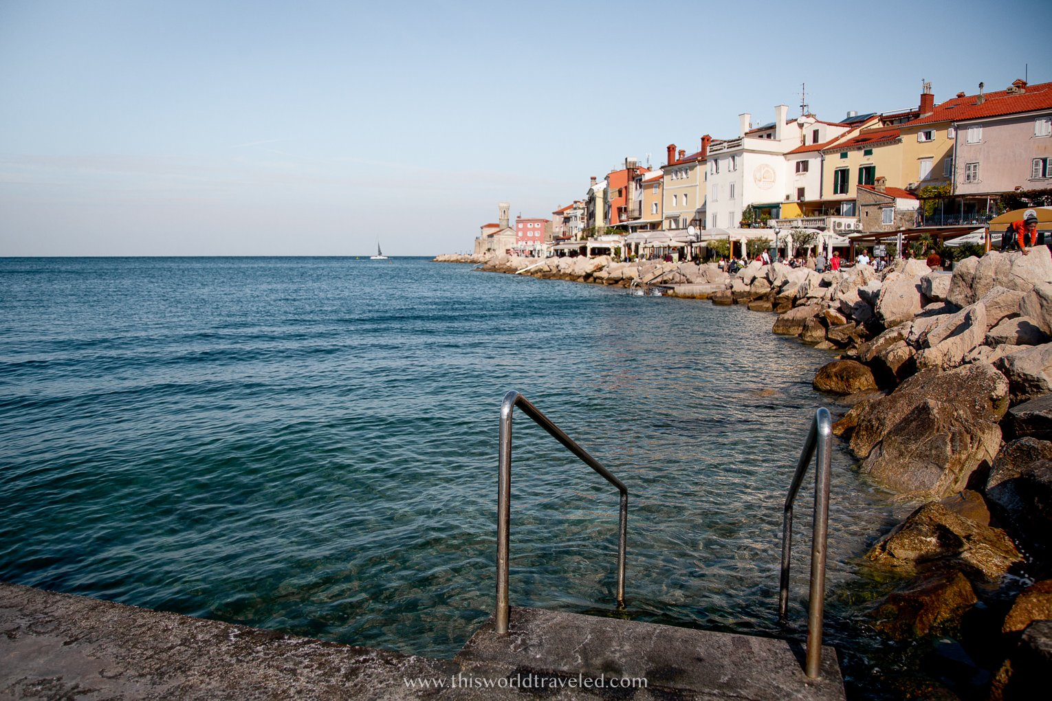 Metal steps leading down into the Adriatic sea alongside large rocks and crystal clear water in Piran, Slovenia